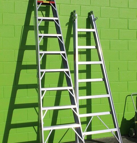 two ladders leaning on a green wall