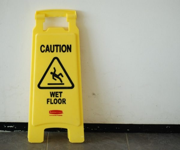 wet floor sign leaning on the wall